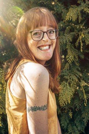 Die Podcasterin Ilka Brühl steht vor einem Busch und lächelt in die Kamera.
